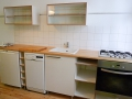 Küche aus Multiplex mit weißer Oberfläche und Glasschiebetüren